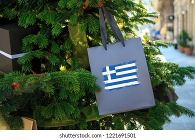 Greek flag printed on a Christmas shopping bag. Close up of a shopping bag as a decoration on a Xmas tree on a street in Greece. Christmas shopping, local market sale and deals concept.