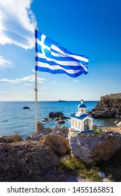 Greek flag and a small church with a boat in the sea for background, Palaiochora, Chania, Crete, Greece.