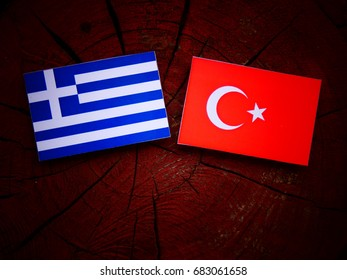 Greek flag with Turkish flag on a tree stump isolated