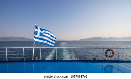 Greek flag waving on a ferry boat crossing the sea