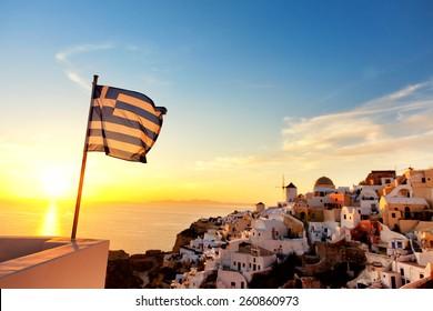 Greek flag waving at sunset in Oia, Santorini, Greece