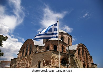 Greek flag waving in the wind with an old byzantine era greek orthodox church in the background