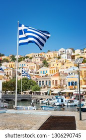 Greek flags, boats and colorful neoclassical houses in harbor town of Symi (Symi Island, Greece)