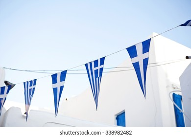 Greek flags on cyclades, traditional white house on background