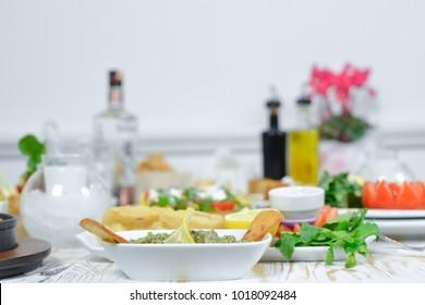 Greek food background. Meze, gyros, fried squid rings, souvlaki, uzo, fish, pita, greek salad, tzatziki, assortment of feta, olives and vegetables. Traditional different greek dishes set.