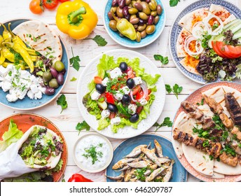 Greek food background. Meze, gyros, souvlaki, fish, pita, greek salad, tzatziki, assortment of feta, olives and vegetables. Traditional different greek dishes set. Top view. Food for share. Close-up