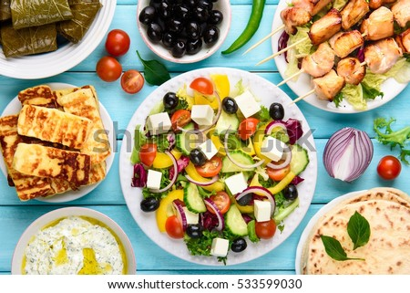 Greek food mix on a blue wooden background. Top view.