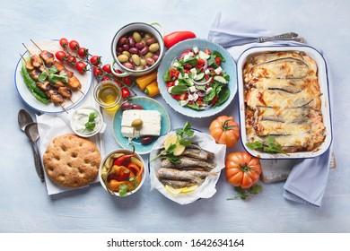 Greek food. Moussaka, meze, souvlaki, fish, pita, greek salad, tzatziki,  olives and vegetables. Traditional different types of greek dishes. Top view