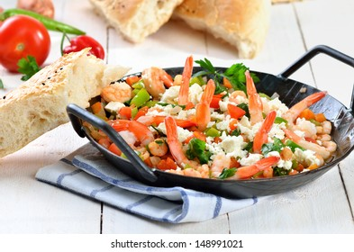 Greek food: Saganaki with shrimps, vegetables and feta cheese