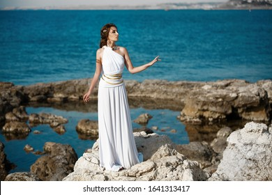 Greek goddess at ancient city ruins. Beautiful young woman Aphrodite style with golden necklace jewelry. Athena walking Greece. Mythical Hellenic creature. Gorgeous girl actress outdoors. Athens myths