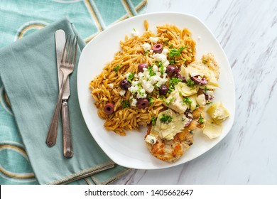 Greek grilled chicken piccata with kalamata olives and artichoke hearts with a side of Mediterranean herbed orzo topped with feta cheese