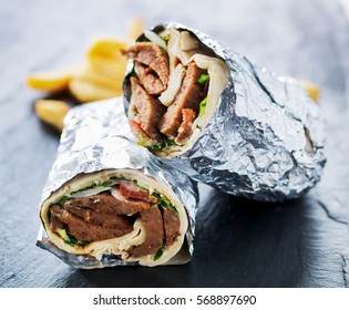 greek gyro wrapped in foil cut in half and served with fries
