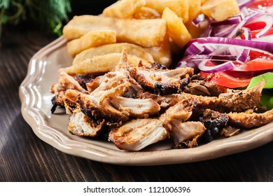 Greek gyros dish with french fries and vegetables. Served with tzatziki sauce