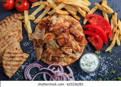 Greek gyros dish on a black plate - top view
