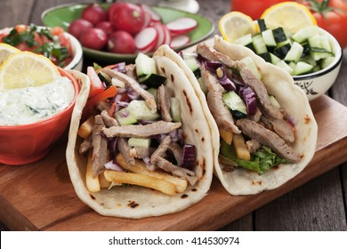 Greek gyros pita wrapped sandwich with meat slices and vegetables