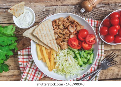Greek gyros platter with french fries, pita, tomato, cucumber and cabbage. Served with tzatziki sauce. Top view. Rustic wooden background
