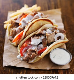 greek gyros with tzatziki sauce and fries on parchment