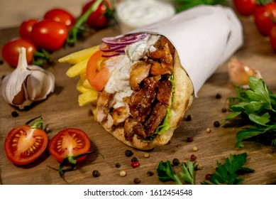 Greek gyros wrapped in pita breads on a wooden background