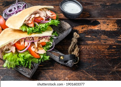 Greek gyros wrapped in pita breads with vegetables and sauce. Dark wooden background. Top view. Copy space.