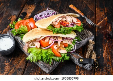 Greek gyros wrapped in pita breads with vegetables and sauce. Dark wooden background. Top view.