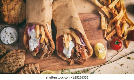 Greek gyros wrapped in pita breads on a wooden background - top view