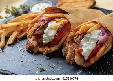Greek gyros wrapped in pita breads on a black plate