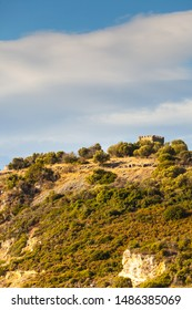 Greek idyllic hills with small shrubs of Mediterranean flora and little castle against cloudy sky.
