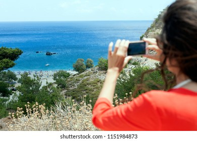 Greek island, Karpathos, young woman taking a panorama photo of the beach with mobile phone