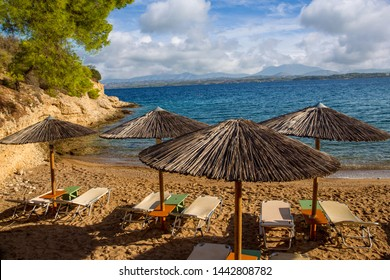Greek island Spetses - beach with awnings .  Idyllic   place  for recreation, not  so noisy  as Mykonos. Fresh  air,   transparent water,  beautiful  beaches.