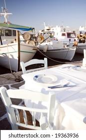 greek island taverna restaurant setting in harbor with classic greece fishing boats