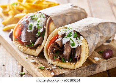 greek lamb meat gyros with tzatziki sauce, feta cheese and french fries