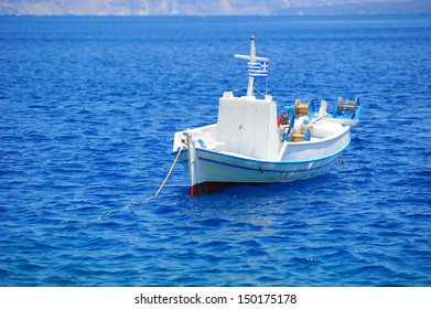 Greek landscape with a white fishing boat (Santorini island)