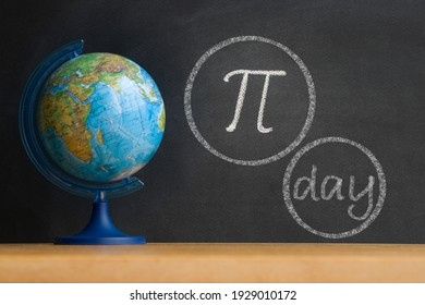 The Greek letter Pi, the ratio of the circumference to its diameter, is drawn in chalk on a black chalkboard in honor of the international number Pi for March 14