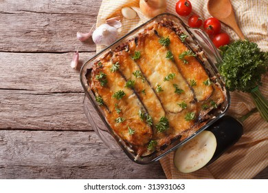 Greek moussaka in baking dish with the ingredients on the table. horizontal view from above