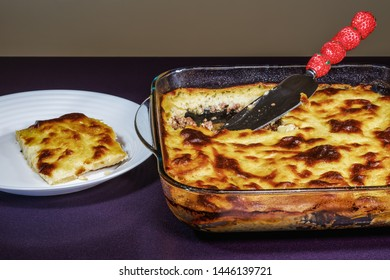 Greek moussaka dish recipe preparation. Ready meal with served portion next to transparent bowl of baked mousaka with bechamel white sauce & fried chopped potatoes above ground chopped beef meat.