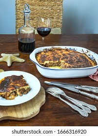 Greek Moussaka . Isolated Image. Homemade traditional Iconic Greek eggplant dish  served on a plate accompanied with a glass of red wine. Stock Image.