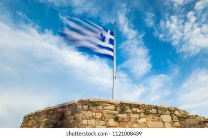 Greek national flag on flagpole waving against blue sky, Acropolis, Athens, Greece