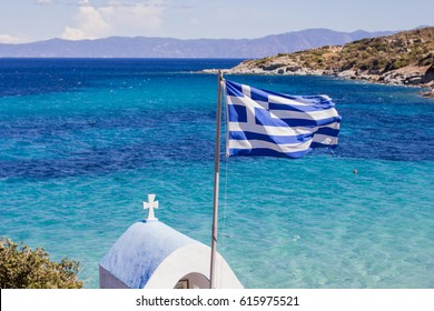 The Greek National Flag over seascape, beautiful turquoise sea , summer travel vacation .