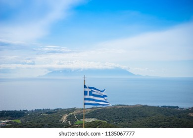 The Greek National Flag waving over seascape and Samothrace island as background, summer travel vacation.