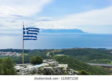 The Greek National Flag waving over seascape and Samothraki island as background, summer travel vacation.