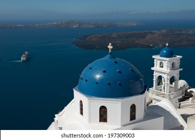 Greek orthodox church with sailboat in Santorini, Greece