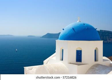 Greek orthodox church with sailboat in Santorini, Greece