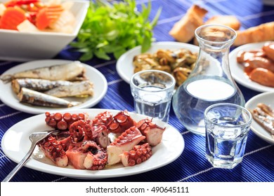 Greek ouzo and meze. Glasses and bottle of ouzo and seafood appetizers
