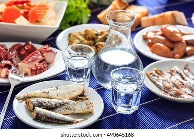 Greek raki and meze. Glasses and bottle of ouzo and seafood appetizers
