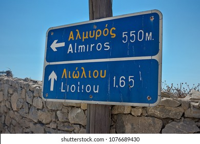 Greek road sign direction - written in Greek and in its Latin alphabet transcription. Shot taken in Schinoussa island