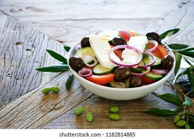 Greek salad in bowl on vintage table. Mediterranean cuisine background