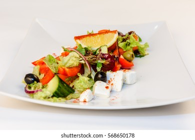 Greek salad close up with feta cheese, tomatoes, olives and green leafs
