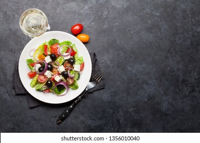 Greek salad with cucumber, tomato, pepper, lettuce, onion, feta cheese and olives, dressed with olive oil. Top view with white wine glass and space for your text