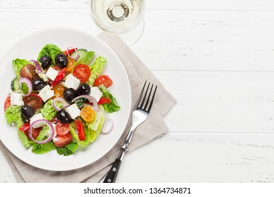 Greek salad with cucumber, tomato, pepper, lettuce, onion, feta cheese and olives, dressed with olive oil. With white wine glass. Top view with copy space