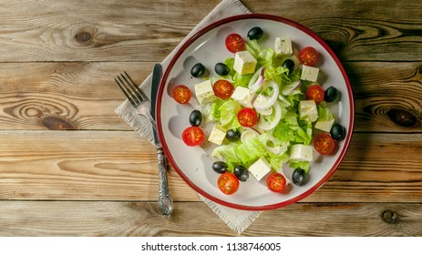 Greek salad with feta cheese, cherry tomatoes and olives in a round plate on a wooden background. Summer menu. Top view